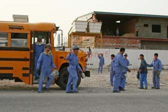 Workers in Qatar exit bus.